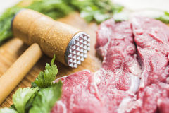 Fresh meat, parsley and a hammer to beat meat Royalty Free Stock Photography