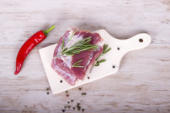 Fresh meat : raw pork meat with red chili pepper, dill and rosemary on wooden board. Fresh meat : raw pork meat with red chili pepper, dill and rosemary on the Stock Photos