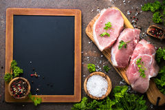 Fresh meat. Raw pork steak. Fresh meat and chalkboard. Ingredients for cooking. Top view with space for your recipes Stock Image