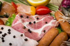 Fresh meat sausages  and vegetables on kitchen board. A set of food, sausages and vegetables Stock Photography