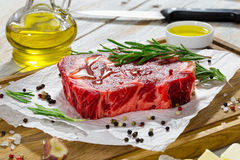 Fresh meat steak poured with olive oil. Raw beef rib eye fresh meat steak on white paper on chopping board with rosemary poured with olive oil. garlic, kosher Stock Images
