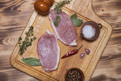 Fresh meat steaks on light wooden cutting board.  Royalty Free Stock Photography