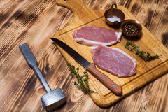 Fresh meat steaks on light wooden cutting board. Toned.  Stock Photo