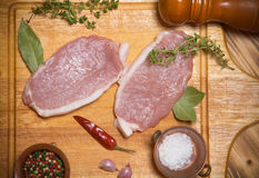 Fresh meat steaks on light wooden cutting board. Toned.  Royalty Free Stock Photos