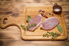 Fresh meat steaks on light wooden cutting board. Toned.  Stock Images