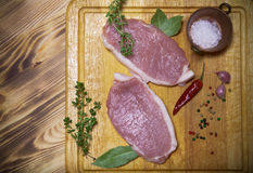 Fresh meat steaks on light wooden cutting board. Toned.  Royalty Free Stock Photo
