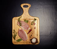 Fresh meat steaks on light wooden cutting board. Toned.  Stock Photos