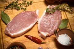Fresh meat steaks on light wooden cutting board. Toned.  Royalty Free Stock Images