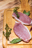 Fresh meat steaks on light wooden cutting board. Toned.  Stock Photography
