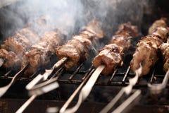 Fresh meat on a steel skewer in a brazier Stock Photo
