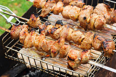 Fresh meat on a steel skewer in a smoke at brazier. Fresh kebabs on skewers grilled over charcoal on the street Stock Image