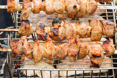 Fresh meat on a steel skewer in a smoke at brazier. Fresh kebabs on skewers grilled over charcoal on the street Royalty Free Stock Image