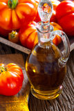Fresh meat tomatoes and a carafe of olive oil Stock Photography