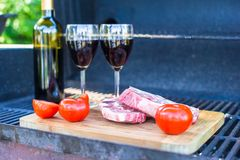 Fresh meat, vegetables and bottle of wine on barbecue outdoors Stock Images