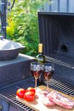 Fresh meat, vegetables and bottle of wine on barbecue outdoors Stock Photo