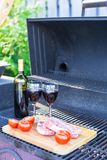 Fresh meat, vegetables and bottle of wine on a picnic outdoors Stock Photo