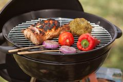 Fresh meat and vegetables on outdoor grill. Fresh meat and vegetables grilled at a summer weekend barbecue Stock Images