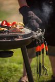 Fresh meat and vegetables on outdoor grill. Fresh meat and vegetables grilled at a summer weekend barbecue, attention on tools for a grill Royalty Free Stock Photography