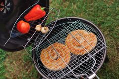 Fresh meat and vegetables on outdoor grill. Sausage pepper and mushrooms on a grill Royalty Free Stock Photo