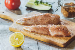 Fresh meat on wooden board. With spice, tomato and lemon on table Stock Photo