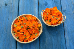 Fresh medical marigold calendula flowers in two basket on blue old   table Stock Image