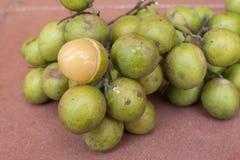 Fresh Melicoccus bijugatus Spanish lime fruit. Closeup bunch of whole fresh Melicoccus bijugatus Spanish limes with one peeled revealing soft juicy pulp on red Royalty Free Stock Photo