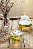 Fresh melissa tea in glass cup, teapot and willow twigs Stock Photo