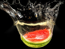 Fresh melon falling in water with splash on black Stock Photography