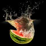 Fresh melon falling in water with splash on black background Royalty Free Stock Photography