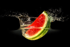 Fresh melon falling in water with splash on black background Royalty Free Stock Photo