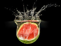 Fresh melon falling in water with splash on black background Royalty Free Stock Image