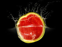 Fresh melon falling in water with splash on black background Stock Photography