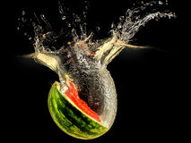 Fresh melon falling in water with splash on black background Stock Images