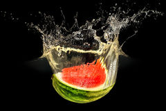 Fresh melon falling in water with splash on black background Stock Image