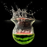 Fresh melon falling in water with splash on black background Stock Photo