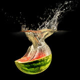 Fresh melon falling in water with splash on black Stock Images