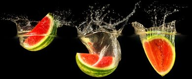 Fresh melon falling in water. With splash on black background Royalty Free Stock Photos
