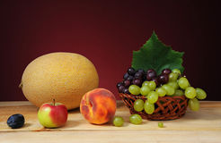 Fresh melon, peaches and grapes in a wicker basket Stock Images