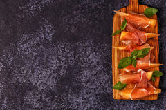Fresh melon with prosciutto and basil. Royalty Free Stock Photography