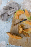 Fresh melon slices with seed on chopping board on rustic background Royalty Free Stock Photo