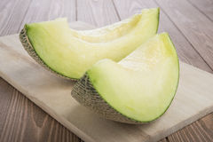 Fresh melons  cantaloupe sliced  on wooden cutting board  and wooden background. Cantaloupe Stock Photography