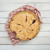 Fresh and Messy Baked Blackberry Pie with Red Plaid Towel on White Shiplap Board Background Table with Square Crop and above, look royalty free stock photos