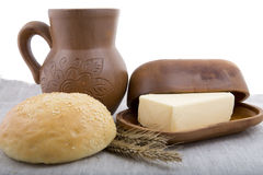 Fresh milk, butter and bun with sesame seeds in a natural potter Stock Photography