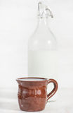 Fresh milk in ceramic mug and closed old fashioned bottle Royalty Free Stock Photography