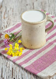 Fresh milk in ceramic mug and flowers Stock Photo