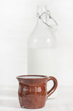 Fresh milk in ceramic mug and open old fashioned bottle Stock Photos