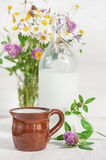 Fresh milk in ceramic mug and wildflowers Royalty Free Stock Image