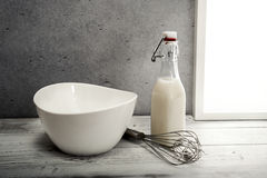 Fresh milk,cream bottle, bowl and wire whisk on window sill Stock Photography