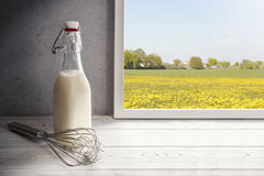 Fresh milk,cream bottle on window sill in countryside Royalty Free Stock Image