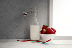 Fresh milk,cream bottle on window sill with strawberries in bowl Royalty Free Stock Photos